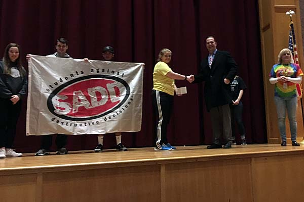 Montgomery County Executive Matthew Ossenfort giving a check to SADD President Jocelyn Hammons.