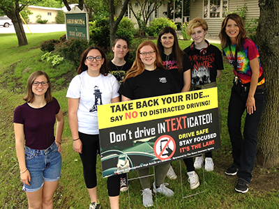 high school students posing in front of don't text and drive poster