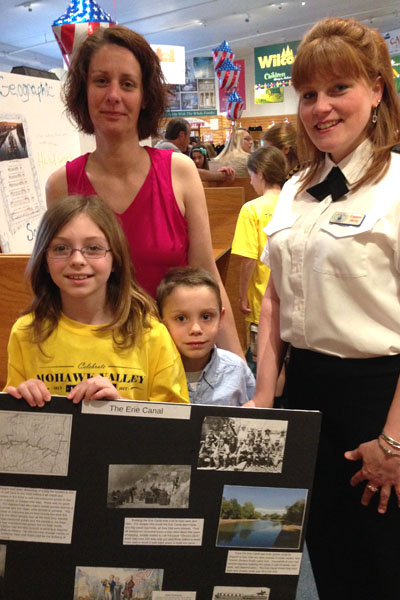 fourth grader with her mom and brother holding a poster