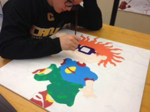 student painting chuckie from cartoon rugrats