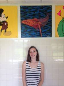 student in front of her painting